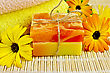 Two Bars Of Homemade Soap, Towels, Marigold Flowers On A Background Of Bamboo Napkins