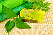 Two Bars Of Homemade Soap, Towels, Nettle Against A Bamboo Napkin stock photo