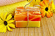 Two Bars Of Homemade Soap Yellow And Orange, Towels, Marigold Flowers On A Background Of Bamboo Napkins