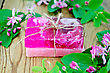 Two Bars Of Soap Homemade Pink, Tied With Twine, Twigs With Leaves And Pink Flowers Of Honeysuckle On A Background Of Wooden Boards