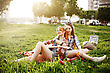 Two Beautiful Young Girls On Picnic In City Park Playing Guitar At The Sunset. Pin Up Vintage Style