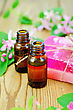 Two Bottles Of Aromatic Oil, Pink Homemade Soap, Branches With Leaves And Pink Flowers Of Honeysuckle On A Background Of Wooden Boards stock photography