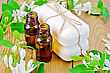 Two Bottles Of Aromatic Oil, Two Bars Of White Soap, Branches With Leaves And White Flowers Of Honeysuckle On A Background Of Wooden Boards stock photo