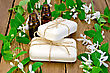 Two Bottles Of Aromatic Oil, Two Bars Of White Soap, Twigs With Leaves And White Flowers Of Honeysuckle On A Background Of Wooden Boards stock image