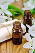 Two Bottles Of Aromatic Oils And White Soap With Flowers Of Apple On A Wooden Boards Background