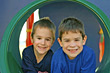Two boys playing laying in a round tunnel stock photography