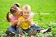 Positive Two Children Are Sitting On Green Meadow And Smile stock photo