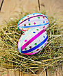 Two Easter Eggs, Decorated With Multicolored Braid And Sparkles As Asterisks In The Hay On The Background Of Wooden Boards stock photo