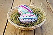 Two Easter Eggs, Decorated With Multicolored Braid And Sparkles In The Hay And A Wicker Basket On A Wooden Boards Background stock image