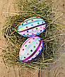 Two Easter Eggs, Decorated With Multicolored Braid And Sparkles As Asterisks In The Hay On The Background Of Wooden Boards On Top stock photo