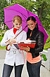 Two Female Students Under Umbrella Outdoors stock image