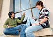 Two Friends Sitting On Windowsill Laughing stock image