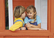 Two Girls Gossiping At A Window stock photo