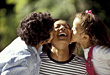 Two girls kissing their mom outside stock photo