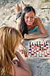 Two Girls Playing Chess On The Beach stock photo