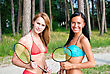 Playful Two Girls Posing With Badminton Rackets On The Beach stock photo