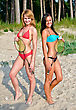 Two Girls Posing With Badminton Rackets On The Beach stock image