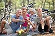 Two Older Couples Enjoying A Picnic In The Woods stock photo