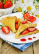 Two Pancakes With Strawberries And Jam On A White Plate, Basket With Berries, Bouquet Of Daisies On A Background Of Wooden Boards stock photo
