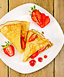 Two Pancakes With Strawberries And Jam On A White Plate On A Wooden Boards Background stock image