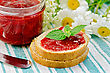 Two Pieces Of Bread With Strawberry Jam, A Jar Of Jam, A Knife And A Bouquet Of Chamomile On A Green Striped Napkin stock image