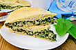 Two Pieces Of Cake With Spinach And Cheese On A Plate, Spinach Leaves, Cup, Knife, Napkin On The Background Of Wooden Boards