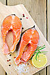 Prepared Food Two Pieces Of Trout With Rosemary, Coarse Salt And Lemon On The Background Of Wooden Boards stock photo