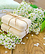 Two Pieces Of White Soap, Flowers, Bird Cherry, A Towel On The Background Of Wooden Boards