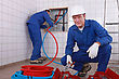 Two Plumbers Working, One Plumber Is Connecting Pipes stock photography