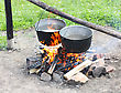 Kitchen Two Pot Hanging Over The Fire. Preparing Food On Campfire In Wild Camping stock photo