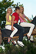 Two Pretty Blonde And Young Man Sitting On A Tree Branch