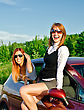 Two Pretty Happy Girls In The Car. Concept Of Carefree Roadtrip