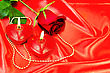 Two Red Candles In The Shape Of A Heart With Golden Ornaments, Red Rose With Green Leaves On A Red Silk stock photo