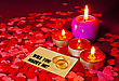 Two Rings And A Card With Marriage Proposal With Four Candles On The Red Background stock photo