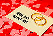 Two Rings And A Card With Marriage Proposal On The Red Background stock photo