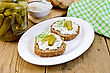 Two Sandwiches With Cream, Pickles And Dill, Jar Of Pickles, A Napkin On Wooden Board stock photo