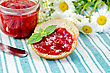 Two Slices Of Bread With Strawberry Jam, A Jar Of Jam, A Knife And A Bouquet Of Daisies On A Green Striped Napkin stock photo