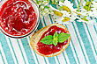 Two Slices Of Bread With Strawberry Jam, A Jar Of Jam, A Bouquet Of Daisies On Green Striped Napkin stock photo