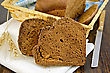Two Slices Of Rye Homemade Bread On A White Napkin With Rye Spikelets, Wicker Basket With Bread, Knife On Dark Wooden Board stock photo