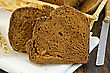 Two Slices Of Rye Homemade Bread On A White Napkin With Rye Spikelet, Wicker Basket With Bread, Knife On A Wooden Board stock photo