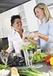 Two Women In Kitchen Preparing Food stock photo