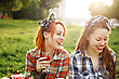 Two Young Happy Girls In Pin-Up Style On Picnic, Laughing, Drinking Wine, Having Fun. Selective Focus