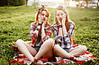Two Young Hipster Girls Dressed In Pin Up Style Having Fun At A Picnic In The Park In The Sunset