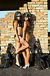 Two Young Playful Women In Helmets Near The Brick Wall