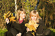Two Young Women With Autumn Leaves In Park