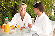 Two Young Women Having Breakfast In The Garden stock photography