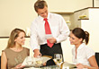 Waiter Serving Female Friends Dining at Restaurant stock photo