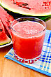Watermelon Juice With A Slice Of Watermelon On A Blue Checkered Napkin Against A Wooden Board stock photo