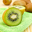 Whole And Half Kiwi, Green Napkin On A Wooden Board stock photo