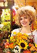 Woman With Blond Curls In Flower Shop, Close Up